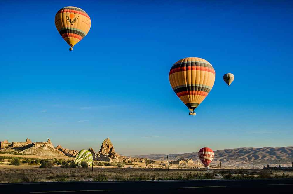 four beige hot air balloons flying